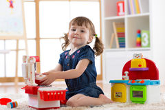 Child playing in nursery with educational toys. Toddler kid in a playroom. Little girl cooking in toy kitchen. Child playing in nursery with educational toys stock images