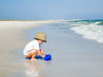 Child Playing by the Ocean Stock Image