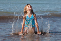 Child playing in the ocean. Cute kid playing in the ocean waves Stock Image