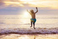 Child playing on ocean beach. Kid at sunset sea. Child playing on ocean beach. Kid jumping in the waves at sunset. Sea vacation for family with kids. Little boy stock photography