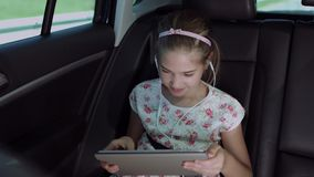 Child playing online game with tablet pc in car. Joyful cute elementary girl in headphones playing online game with digital tablet while sitting in the back seat stock footage