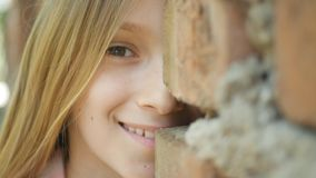 Child Playing Outdoor, Kid Spying, Girl Portrait Laughing Behind Walls, Smiling royalty free stock photos