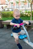 Child playing on outdoor playground in summer. Kids play on kindergarten yard. Active kid holding swing and a pink scoop stock photo