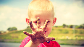 Child playing outdoor showing dirty muddy hands. Stock Photos