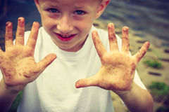 Child playing outdoor showing dirty muddy hands. Stock Image