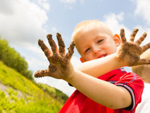 Child playing outdoor showing dirty muddy hands. Child little blonde boy kid playing outdoor showing dirty muddy hands. Happy childhood Stock Photo