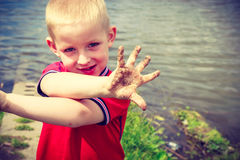 Child playing outdoor showing dirty muddy hands. Royalty Free Stock Image