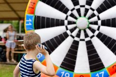 Child playing outdoor - throwing to target. Child playing outdoor - throwing objects to target Royalty Free Stock Photos