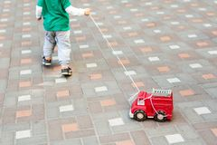 Child playing outdoors. Kid carrying rope with red fire engine toy truck. Children street games royalty free stock photos