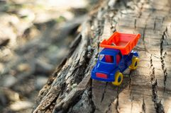 Child playing outdoors. Kid we pour the sand into the red truck. Children street games A boy playing with a machine on the big log royalty free stock photo