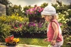 Child playing outdoors in summer countryside blossoming backyard concept happy childhood. Child girl playing outdoors in summer countryside blossoming backyard Royalty Free Stock Photos