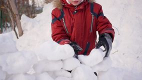 Child playing outdoors in winter. The child builds a wall of snow stones stock video
