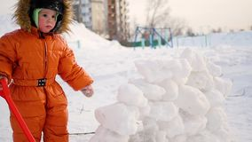 Child playing outdoors in winter. The child builds a wall of snow stones stock footage