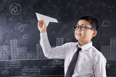 Child playing paper airplane in class. Portrait of a cute schoolboy playing a paper airplane in the classroom Royalty Free Stock Images