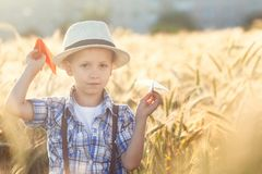 Child playing with paper airplane dreams of traveling in summer day in nature stock images