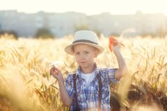 Child playing with paper airplane dreams of traveling in summer day in nature royalty free stock photos