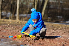 Child playing with paper boats in spring water Stock Photos