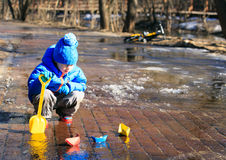 Child playing with paper boats in spring water Royalty Free Stock Image