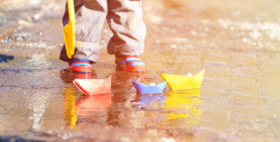 Child playing with paper boats in spring water Stock Images