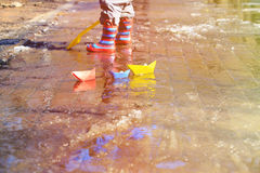 Child playing with paper boats in spring water Royalty Free Stock Photo