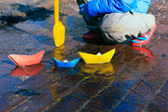 Child playing with paper boats in spring water Stock Photography