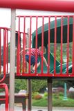 Child Playing at Park. Young boy going to take a ride down a slide in playground Stock Photography