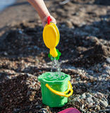 Child playing on a pebbly beach. With toys Royalty Free Stock Image