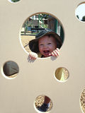 Child Playing Peekaboo at the Playground. Child laughing and playing Peekaboo at the Playground on a sunny day Royalty Free Stock Images