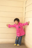 Child playing and peeking. Asian little girl peeking in a corner Royalty Free Stock Photo