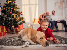Child playing with pet on holiday. I like celebrating Christmas with my family. Joyful boy is lying in floor with dog and smiling royalty free stock images