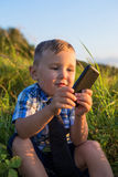 A child playing with the phone Stock Images