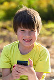 Child playing phone outdoors Royalty Free Stock Image