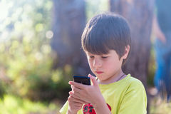 Child playing phone outdoors Royalty Free Stock Images