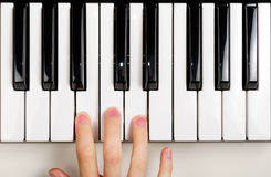 Child Playing the Piano. The hand of a child playing the piano (MIDI keyboard Royalty Free Stock Images