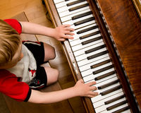 Child playing piano. Child on bench playing old wooden piano