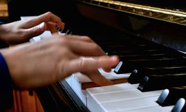 Child playing piano. Close up side view blurred hands and fingers playing a song stock photography