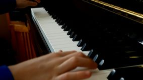 Child playing piano. Close up side view of young hands and fingers playing a song on the keys. Child playing piano. Close up side view of young hands and stock video