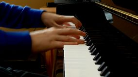 Child playing piano. Close up side view of young hands and fingers playing a song on the keys. Child playing piano. Close up side view of young hands and stock video footage