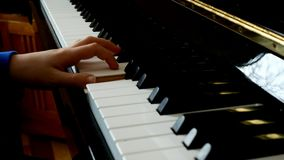 Child playing piano. Close up side view of young hands and fingers playing a song on the keys. Child playing piano. Close up side view of young hands and stock footage
