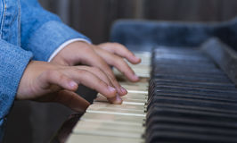 Child playing piano with selective focus and Royalty Free Stock Photo