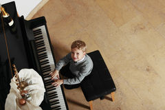 Child playing the piano smiling Stock Image