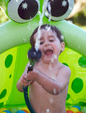 Child playing in plastic pool. Boy looking up as he plays in a green plastic pool during summer. Lots of multicolored plastica ball float around him Royalty Free Stock Photos