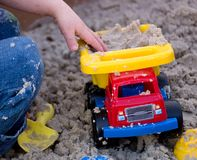 Child Playing with Plastic Truck in Sand. Child Playing with Red, Yellow, and Blue Plastic Truck in Sand stock image