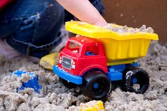 Child Playing with Plastic Truck in Sand. Child Playing with Yellow, Red, and Blue Plastic Truck in Sand royalty free stock image