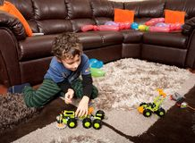 Child playing with plastic trucks Stock Photography