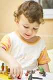 Child playing with plasticine. Girl child playing at home with plasticine making different objects an animals Stock Photography