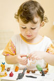 Child playing with plasticine. Girl child playing at home with plasticine making different objects an animals Royalty Free Stock Image