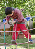 Child playing at playground. Child playing at children playground, climbing on  rope ladder obstacle course equipment Stock Image
