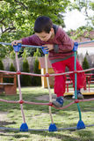 Child playing at playground. Child playing at children playground, climbing on  rope ladder obstacle course equipment Royalty Free Stock Photo