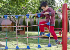 Child playing at playground. Child playing at children playground, climbing on  rope ladder obstacle course equipment Stock Photos
